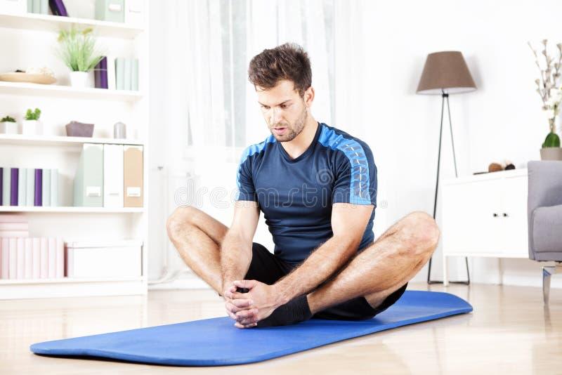 在家做供以座位的内收肌舒展的运动人 免版税库存照片