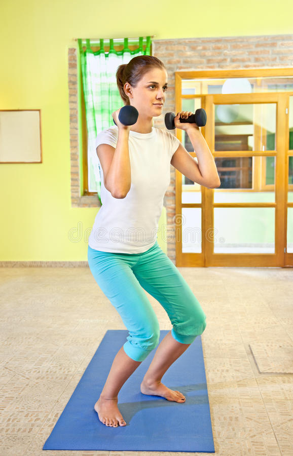 在家做健身的愉快的少妇。 免版税库存图片
