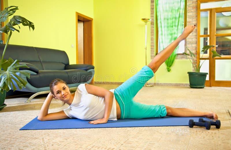 在家做健身的愉快的少妇。 免版税图库摄影