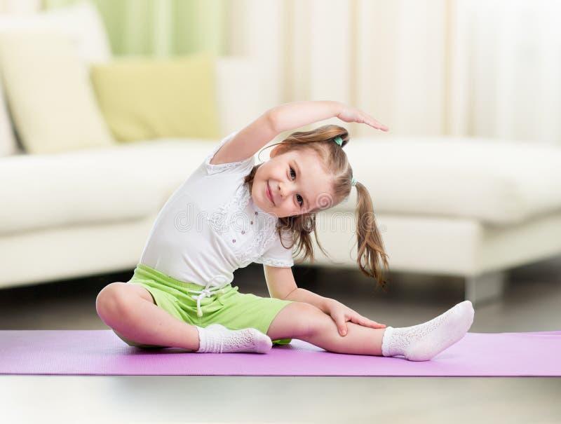 在家做健身锻炼的孩子在客厅 库存照片
