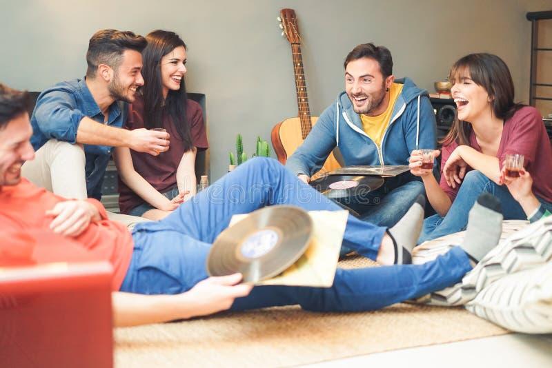 在家做党听的葡萄酒乙烯基圆盘-年轻人的小组愉快的朋友有乐趣饮用的射击 免版税图库摄影