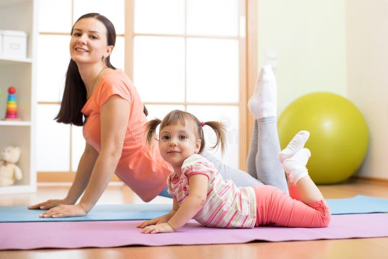 在家做在地板上的母亲和儿童女儿瑜伽锻炼在屋子里 家庭获得乐趣户内与健身 库存图片
