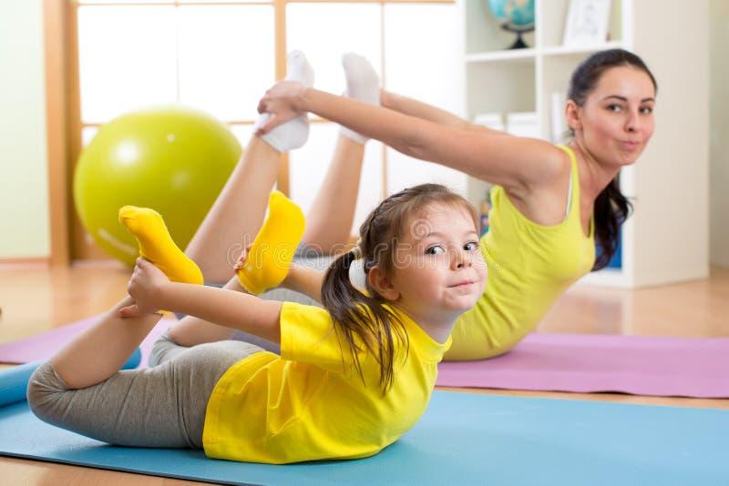 在家做在地毯的母亲和孩子健身锻炼 免版税库存图片