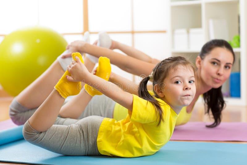 在家做在地毯的母亲和孩子瑜伽锻炼 免版税库存照片