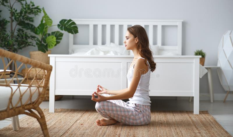 在家做在莲花坐的年轻美女瑜伽 免版税库存图片