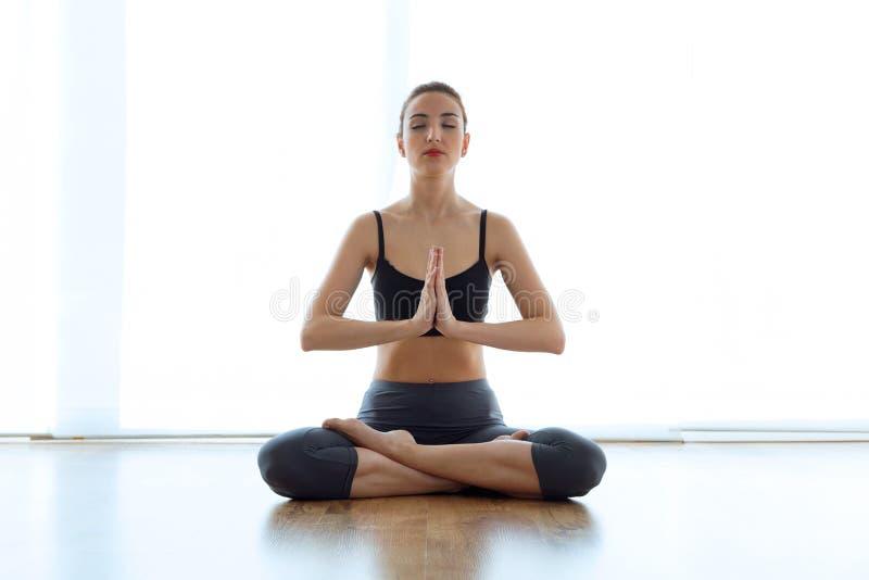 在家做在莲花坐的美丽的运动的少妇瑜伽 免版税库存图片