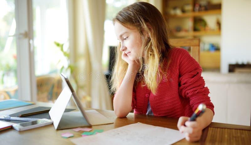 在家做她的与数字片剂的聪明的青春期前的女小学生家庭作业 使用学习的小配件的孩子 图库摄影