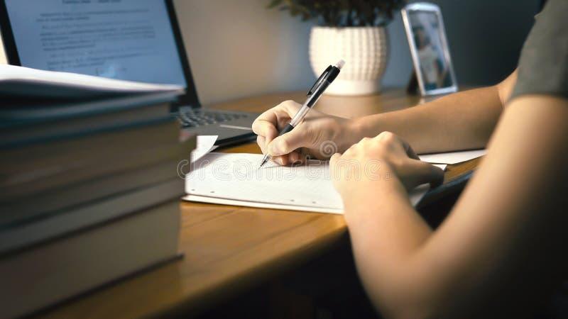 在家做学校家庭作业的学院或大学生 后工作在晚上 在纸的年轻女人文字与笔 免版税库存照片