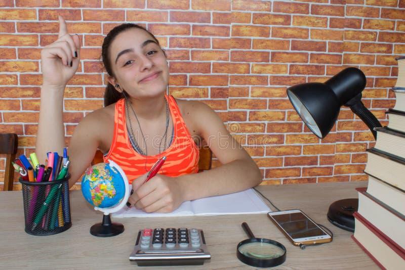 在家做家庭作业的微笑的少年女孩在桌上 有堆的学习的女学生书和笔记户内 图库摄影