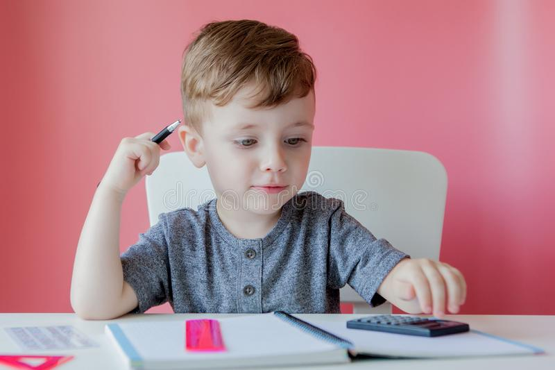 在家做家庭作业的逗人喜爱的孩子男孩画象  一点写与五颜六色的铅笔的被集中的孩子,户内 ?? 免版税库存照片
