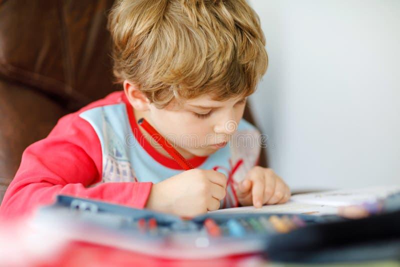 在家做家庭作业的逗人喜爱的愉快的学校孩子男孩画象  与五颜六色的铅笔的小孩文字,户内 库存图片