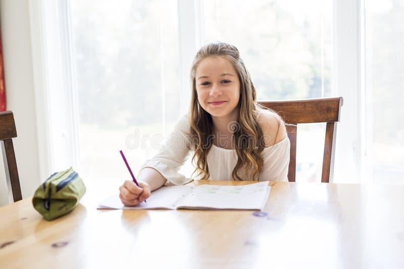 在家做家庭作业的逗人喜爱的青少年的女孩 库存图片