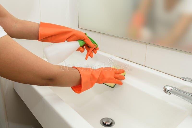在家做差事的妇女在卫生间里,清洗水槽和龙头 库存照片