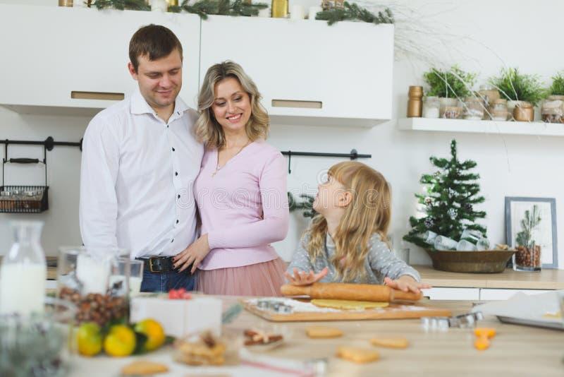 在家做曲奇饼的年轻家庭 食物、家庭、圣诞节、hapiness和人概念-做a的微笑的家庭 免版税库存照片