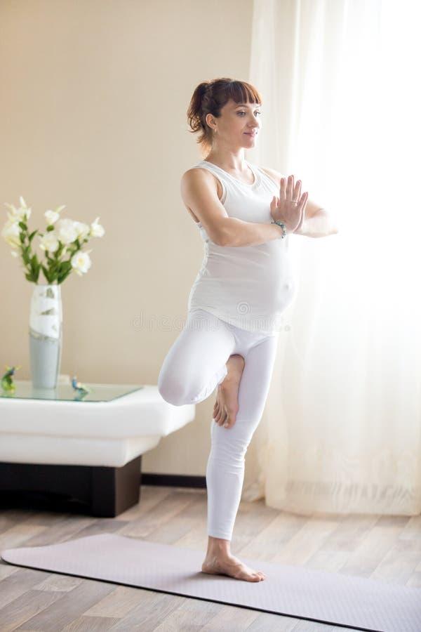 在家做树瑜伽姿势的孕妇 免版税库存照片