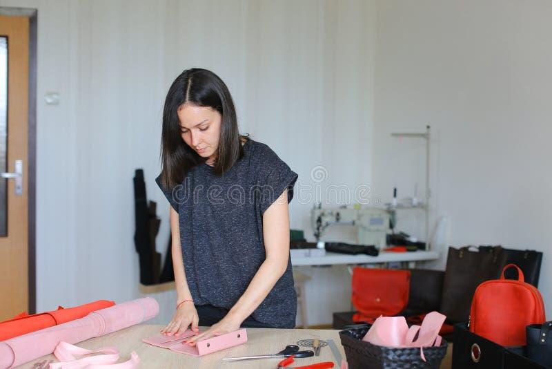 在家做桃红色皮革钱包工作室的少妇 免版税库存照片