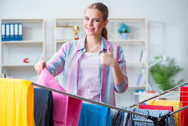 在家做洗衣店的年轻主妇 免版税图库摄影