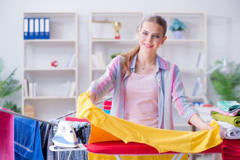 在家做洗衣店的年轻主妇 免版税库存照片