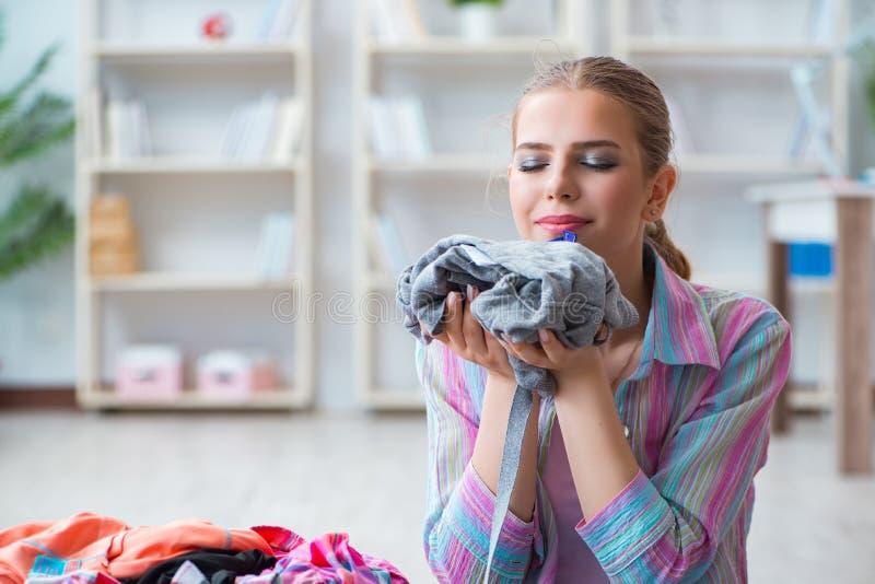 在家做洗衣店的年轻主妇 免版税库存图片