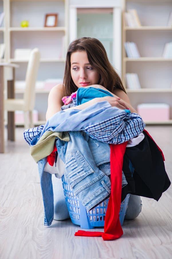 在家做洗衣店的被注重的妇女 库存照片