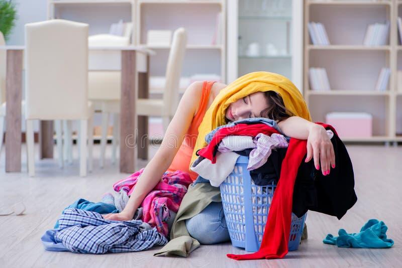 在家做洗衣店的被注重的妇女 免版税库存图片