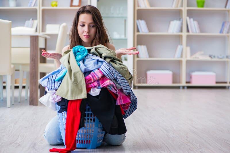在家做洗衣店的被注重的妇女 免版税图库摄影