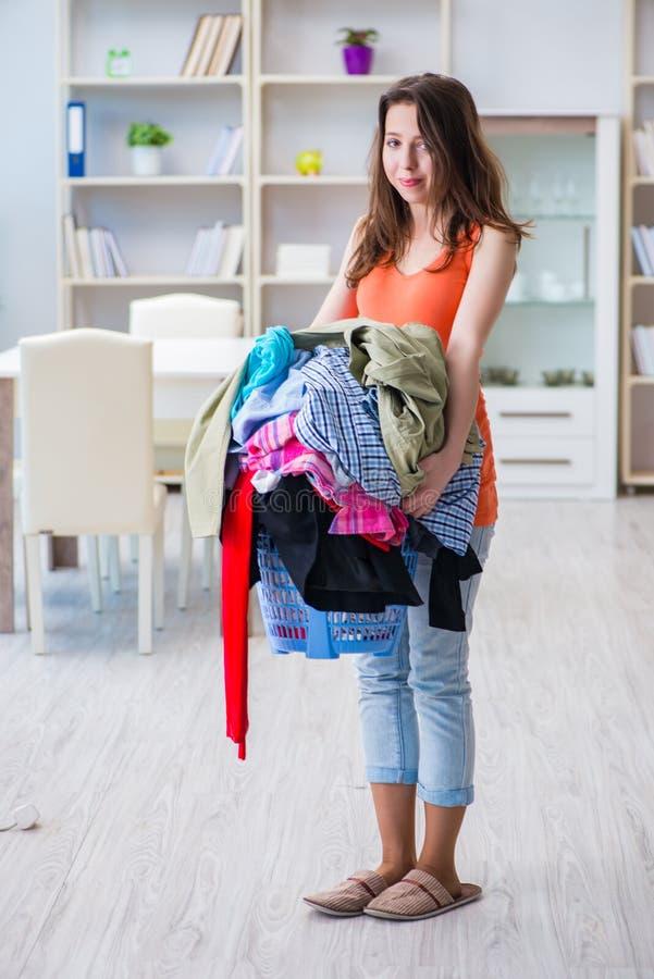 在家做洗衣店的被注重的妇女 图库摄影