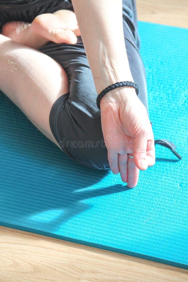 在家做瑜伽姿势- asana -在阳光下的年轻女人 免版税库存照片