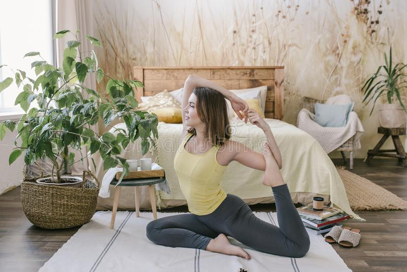 在家做瑜伽锻炼的妇女在她轻的时髦的卧室 早晨锻炼在卧室 健康和体育生活方式 库存图片