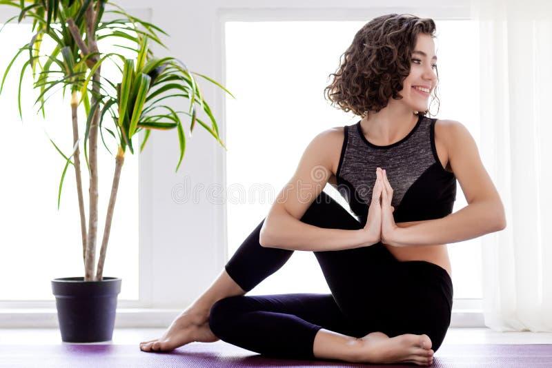 在家做瑜伽锻炼的年轻女人 免版税图库摄影