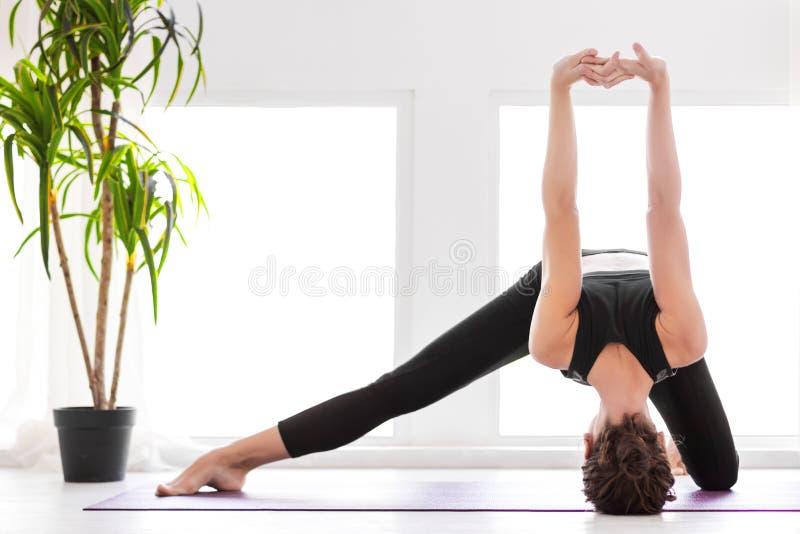 在家做瑜伽锻炼的年轻女人 库存照片