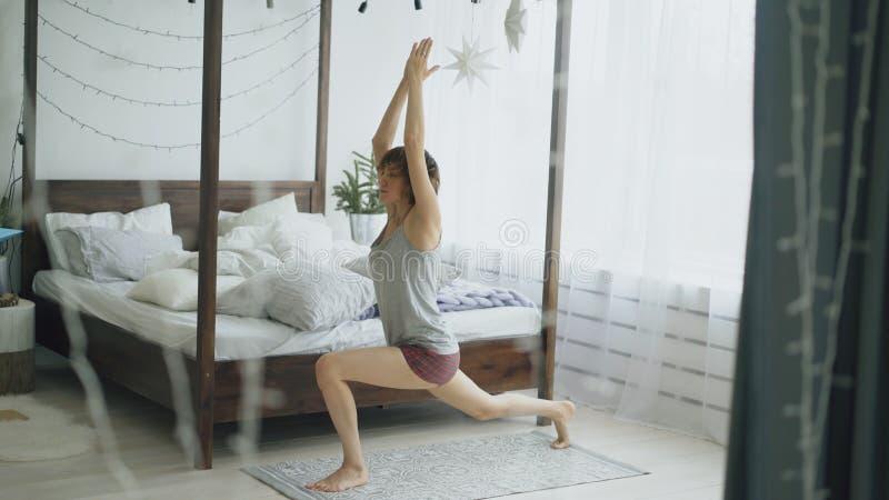 在家做瑜伽锻炼的年轻美丽的妇女在床附近在卧室 图库摄影
