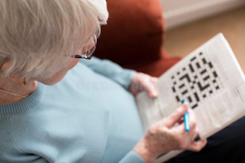 在家做纵横填字游戏的资深妇女 免版税库存图片