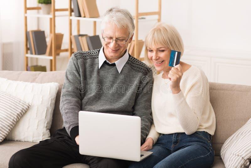在家做网络购物的愉快的更旧的夫妇 免版税库存照片