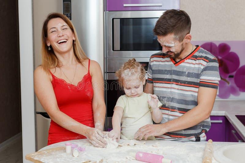 在家做面团厨房的母亲、父亲和女儿 免版税库存照片