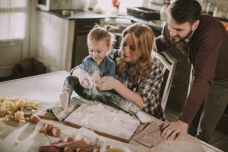 在家做面团的愉快的家庭在厨房里 库存图片