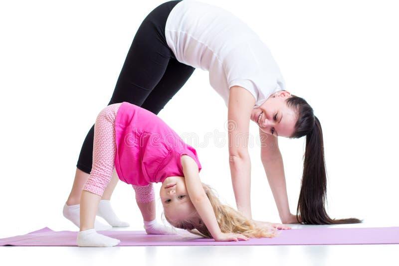 在家做锻炼的母亲和孩子 免版税图库摄影