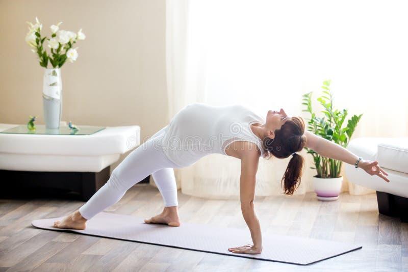 在家做Camatkarasana瑜伽姿势的孕妇 库存图片