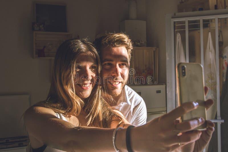 在家做selfie的人和女孩夫妇  做与滑稽,微笑的面孔的人和女孩一selfi 图库摄影