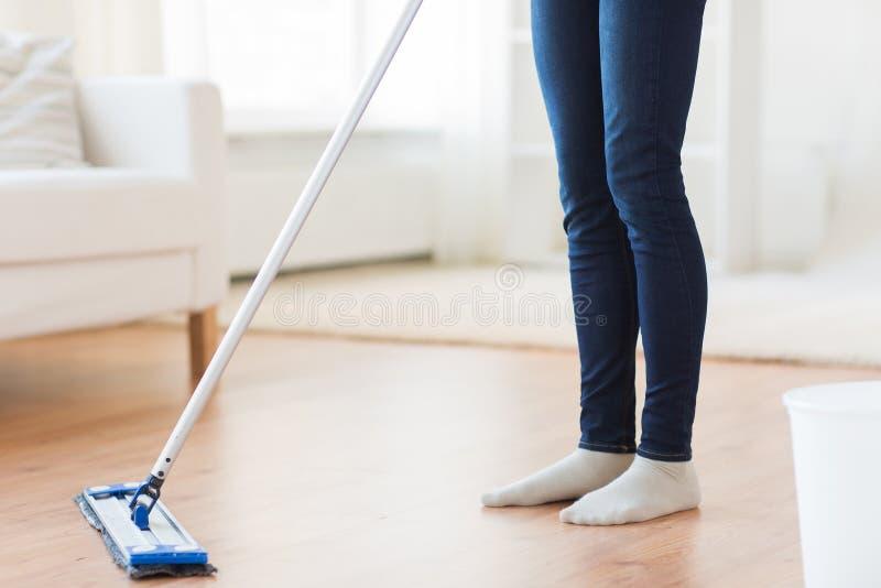 在家关闭有拖把清洁地板的妇女 免版税库存照片