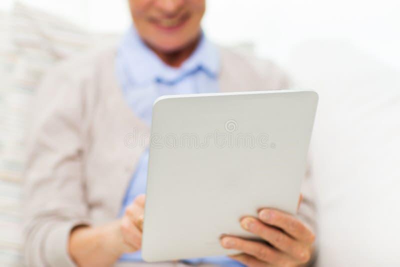 在家关闭有片剂个人计算机的资深妇女 库存图片