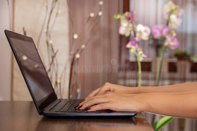 在家写博克的妇女在一张木书桌上的一台膝上型计算机 免版税库存图片
