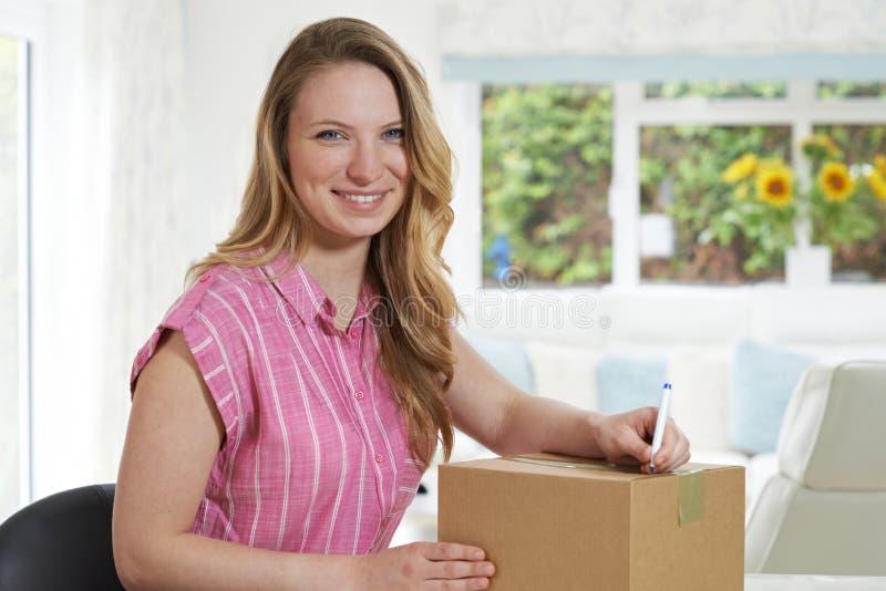 在家写地址的妇女画象在包裹 库存照片
