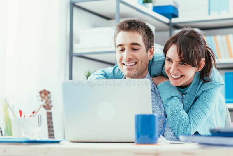在家冲浪万维网的年轻夫妇 免版税库存图片