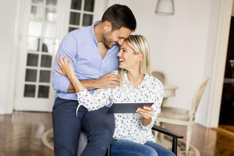 在家冲浪在片剂上的网的年轻愉快的夫妇 免版税图库摄影