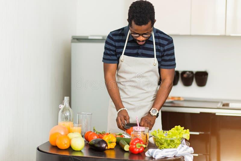 在家准备健康食品的非洲人在厨房里 免版税库存照片