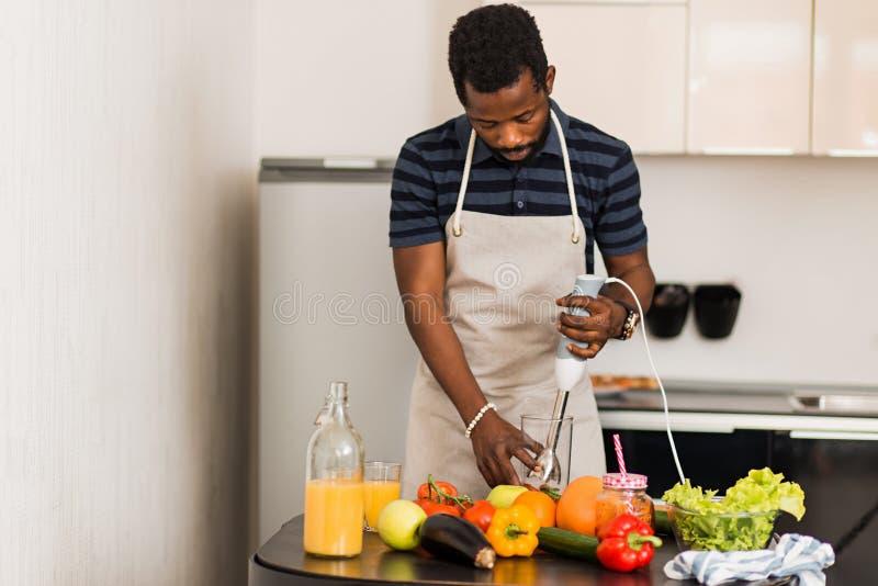 在家准备健康食品的非洲人在厨房里 免版税库存图片