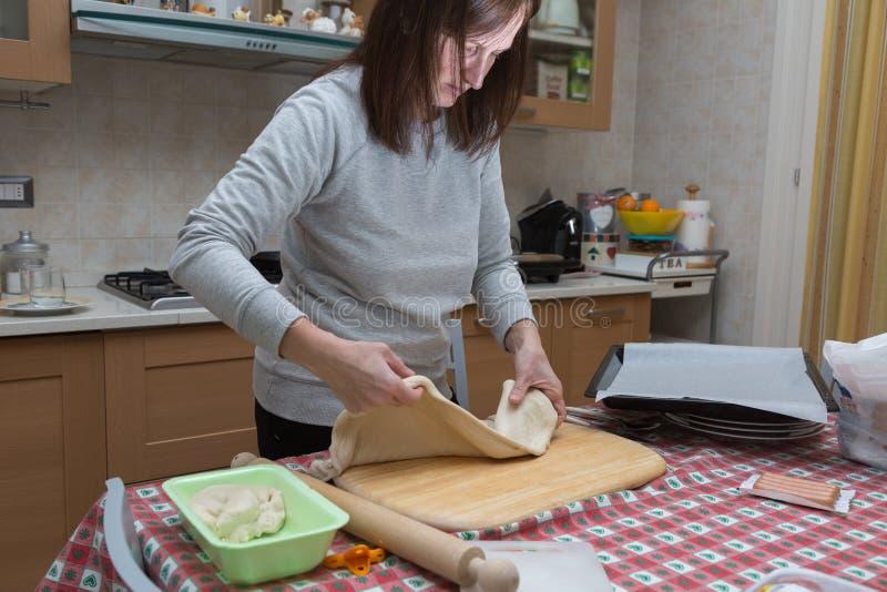 在家准备比萨:做一可口比萨的妇女在厨房里 免版税库存照片