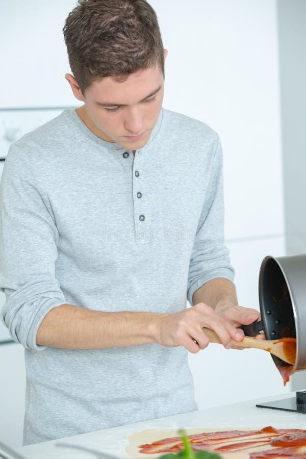 在家准备薄饼的年轻人 免版税库存照片