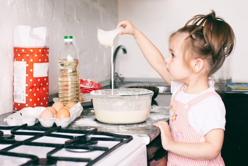 在家准备面团的一个小逗人喜爱的女孩在厨房里 库存照片